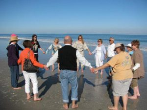 students doing reiki energy healing on the beach and ocean